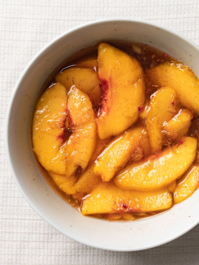 Syrupy peaches in bowl for Fluffy Homemade Maple Peach Pancakes via forkknifeswoon.com