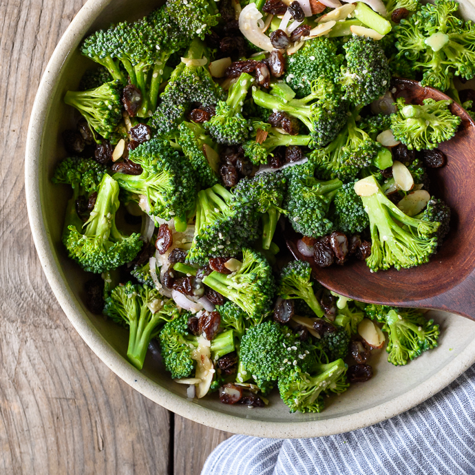 Fresh and healthy Broccoli Salad with Raisins, Almonds, and a Lemon Tahini Dressing via forkknifeswoon.com