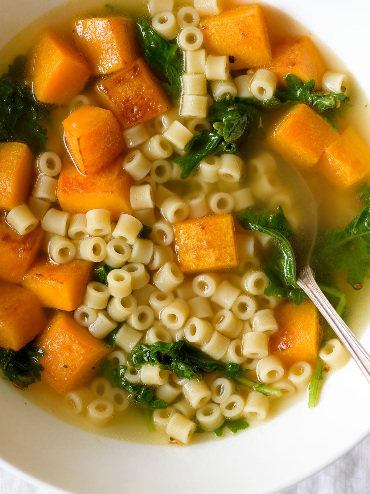 Closeup of a white bowl of butternut squash noodle soup.