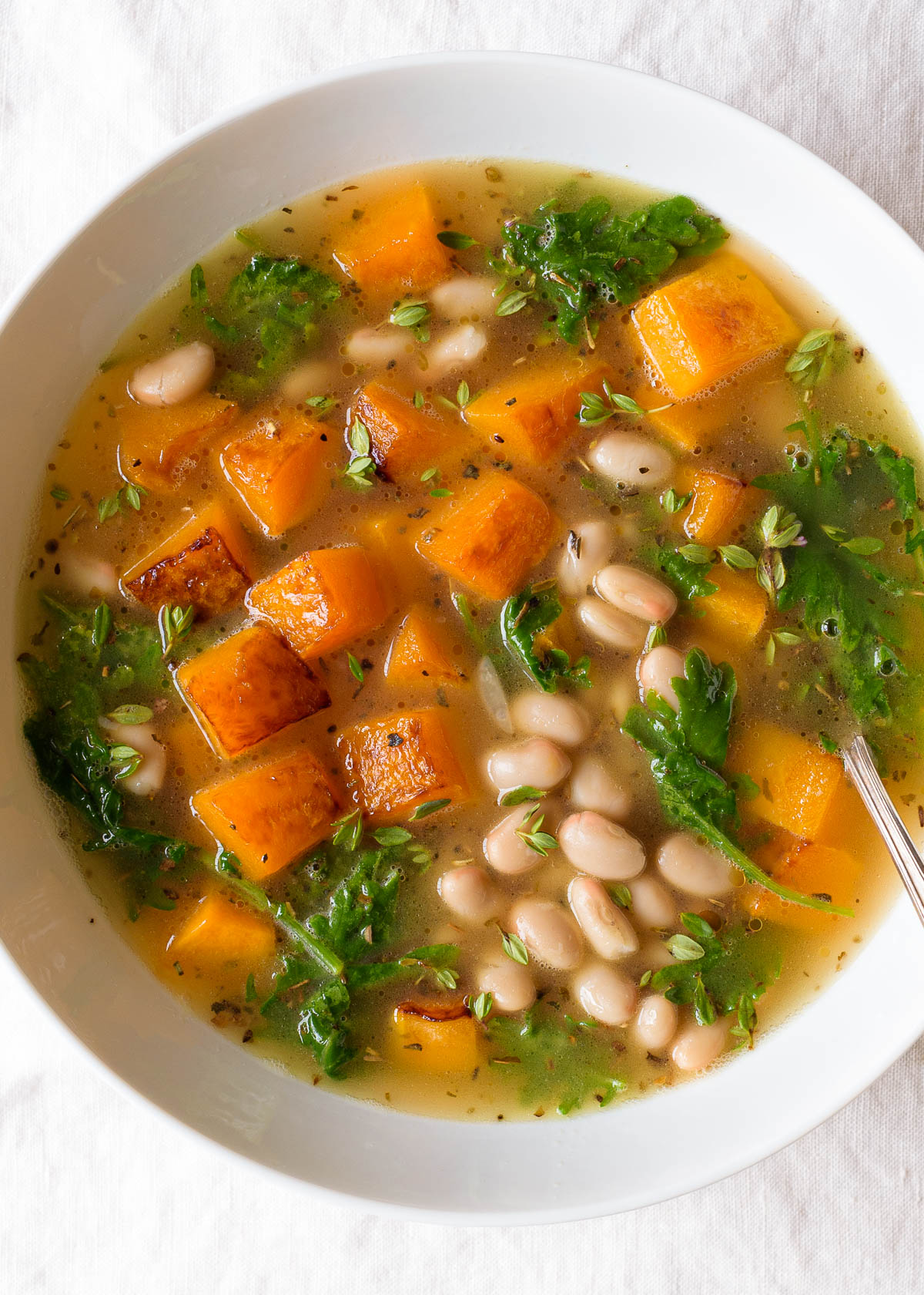 A bowl of white bean and butternut squash soup with kale.