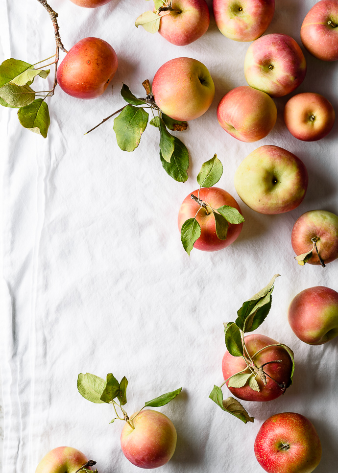 freshly picked apples on a white linen tablecloth