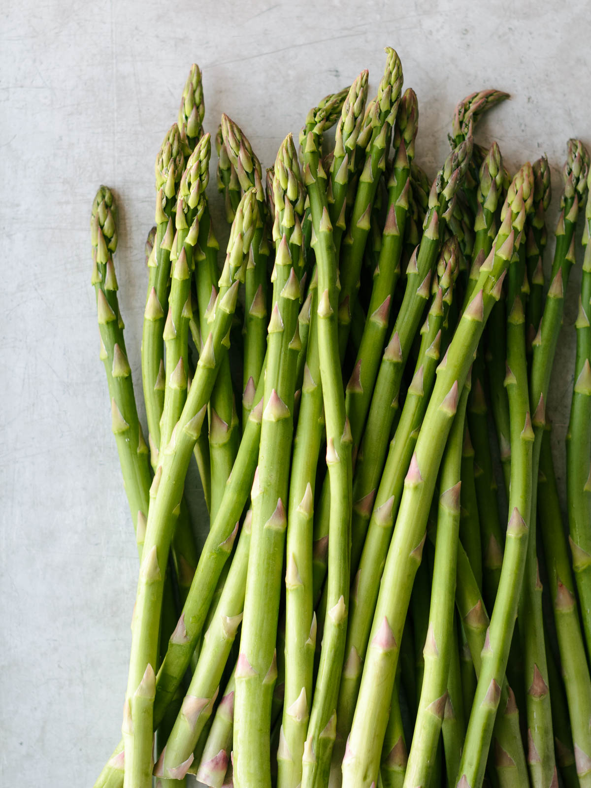 a pile of tender spring asparagus on a sheet pan