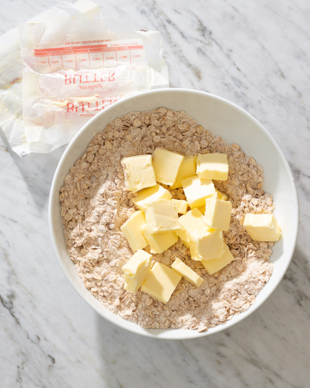 adding softened butter cubes to the dry ingredients to make a crumb bar crust in a mixing bowl from forkknifeswoon.com