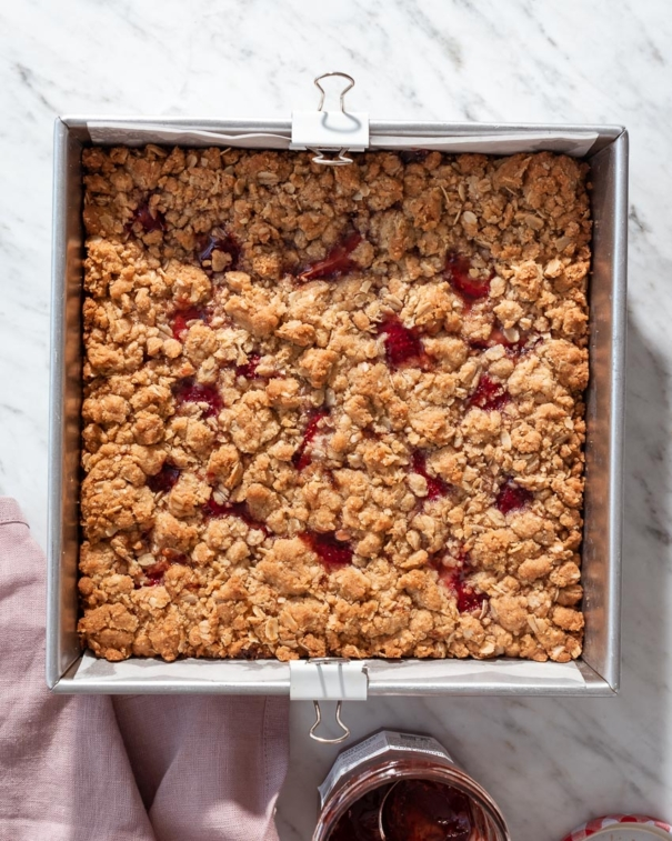 strawberry jam crumble bars in a baking pan, ready to be cutfrom forkknifeswoon.com